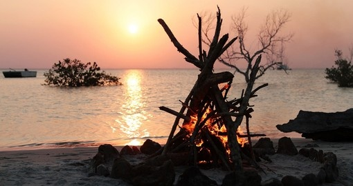 A beautiful camp fire on a tropical beach at sunset