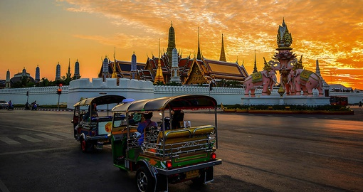 Tuk tuk zooming by one of Bangkok's many temples