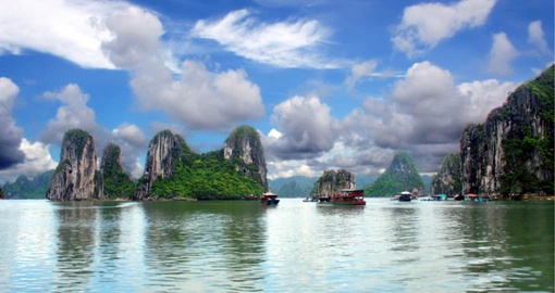 Limestone pillars and tiny islands dot the emerald waters of Halong Bay