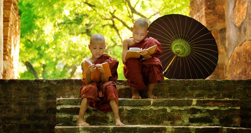 Young buddhist monks reading outdoors sitting outside monastery